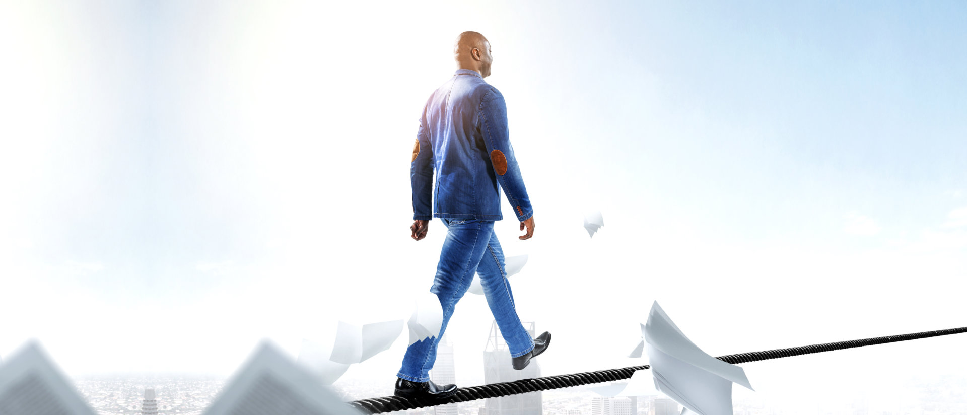 man blindfolded walking across a rope attached
